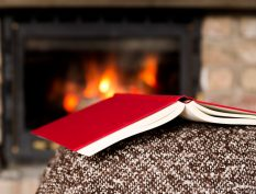 Book resting on a couch beside the fire