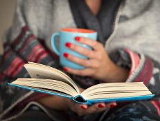Reading a book with a coffee mug