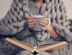 Woman with a blanket, book, and coffee mug