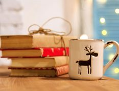 Stack of gift-wrapped books with a mug