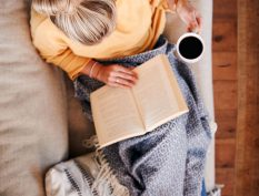 Woman reading on couch with coffee