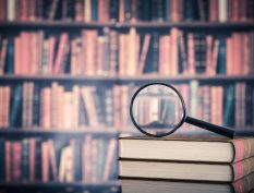 Magnifying glass on a pile of books