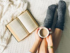 Reading and holding coffee with blanket