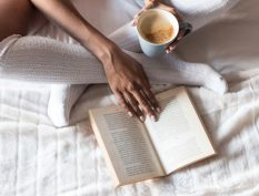 Reading in bed with a cup of coffee