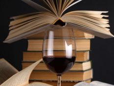 Glass of red wine with books