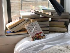 In a Book Club Far Away Book beside a window