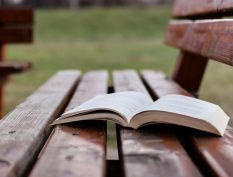 Open book on a rainy park bench