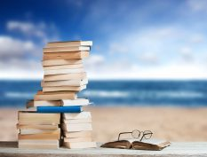 Books stacked beside a beach