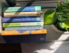 Books by Fredrik Backman beside a window