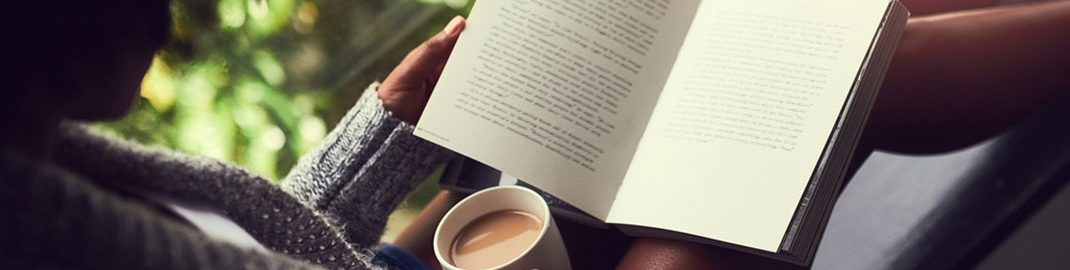 Reading by a window with a cup of coffee