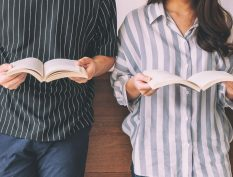 Two People Reading Books Beside Each Other